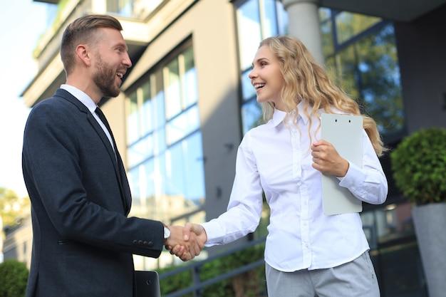 ドキュメントについて話し合ったり、オフィスの近くで握手したりする同僚の画像。