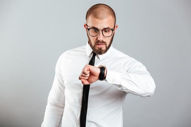 Изображение концентрированного взрослого мужчины 30-х годов в деловой костюм, глядя на наручные часы, изолированных на серую стену