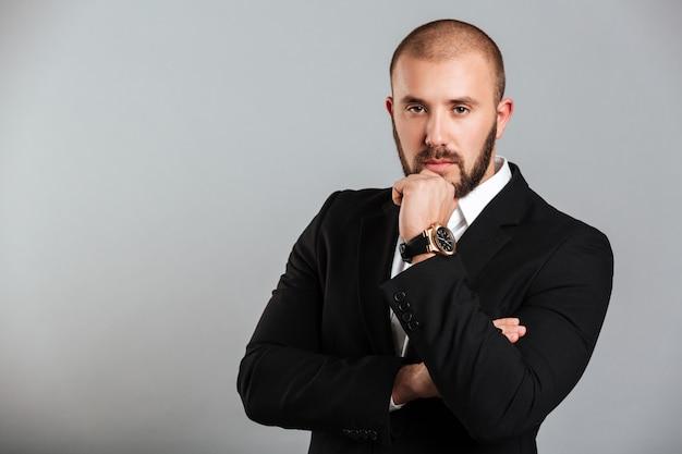 Изображение сконцентрированного взрослого человека в черном деловом костюме, касающегося его подбородка и позирующего осмысленным взглядом, изолированного над серой стеной