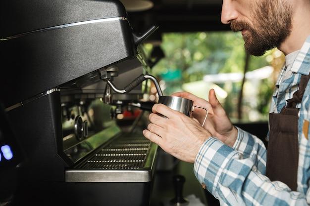 屋外のカフェや喫茶店で働いているときにコーヒーを作るエプロンを身に着けている集中バリスタ男性の画像