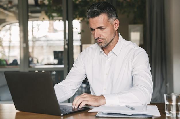 문서 및 노트북으로 작업하는 동안 사무실에서 테이블에 앉아 흰 셔츠를 입고 집중된 자신감 사업가 30 대의 이미지