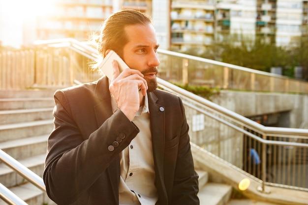 スマートフォンで話しているとダウンタウンの階段に立っている間、商談をしているフォーマルスーツで集中してヨーロッパ人30代のイメージ