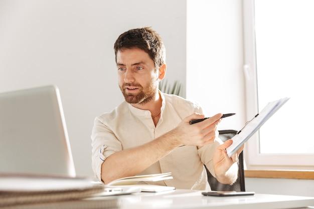 Изображение сосредоточенного офисного парня 30-х годов в белой рубашке с ноутбуком и бумажными документами, работающего на современном рабочем месте