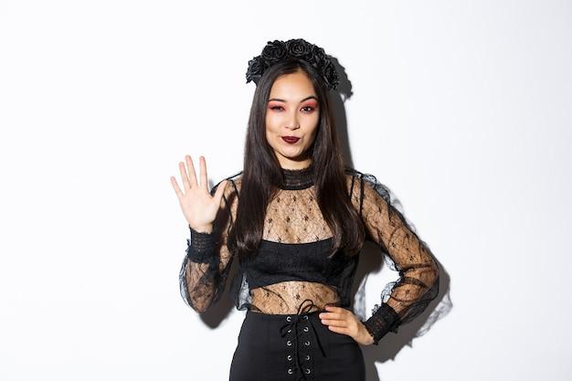 Изображение уверенно красивой азиатской женщины в костюме хеллоуина показывает пять пальцев, поднимая руку, чтобы поздороваться, стоя над белой предпосылкой.