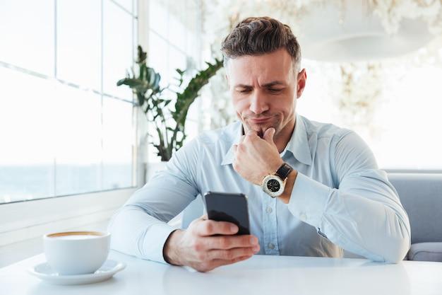 Изображение уверенного делового человека, сидящего в одиночестве в городском кафе с чашкой капучино и просматривающего интернет в черном смартфоне