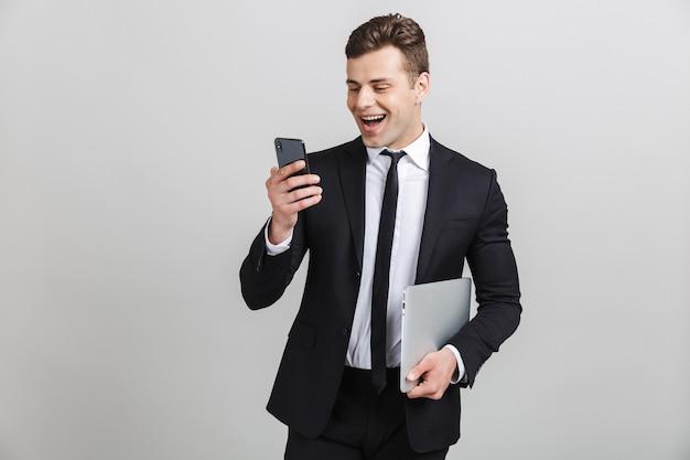 Изображение уверенно счастливого бизнесмена в строгом костюме, печатающего на мобильном телефоне и держащего ноутбук изолированным