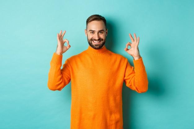 Изображение уверенно улыбающегося человека, показывающего нормальный знак, одобряющего и согласного, гарантирующего качество, стоящего над светло-бирюзовой стеной.