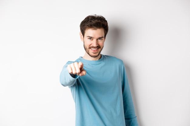 Изображение уверенного в себе молодого человека, улыбающегося и указывающего на камеру, приглашающего и выбирающего вас, манит присоединиться к нему, стоя на белом фоне.