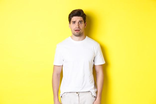 黄色の背景に立って、何か奇妙な、眉をひそめている不安を見て混乱し、神経質な男の画像。