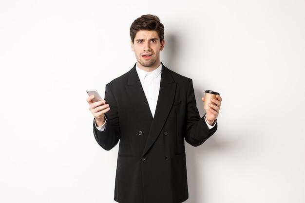 양복을 입고 커피와 휴대폰을 들고 서 있는 혼란스러운 사업가의 이미지, 흰색 배경에 서서 무언가를 이해할 수 없다