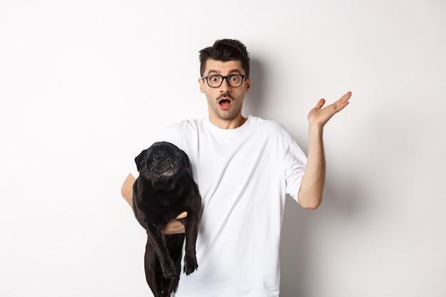 犬を抱き、肩をすくめる、わからない、困惑した手を上げて、白い背景の上に彼の動物と一緒に立っている混乱した流行に敏感な男の画像