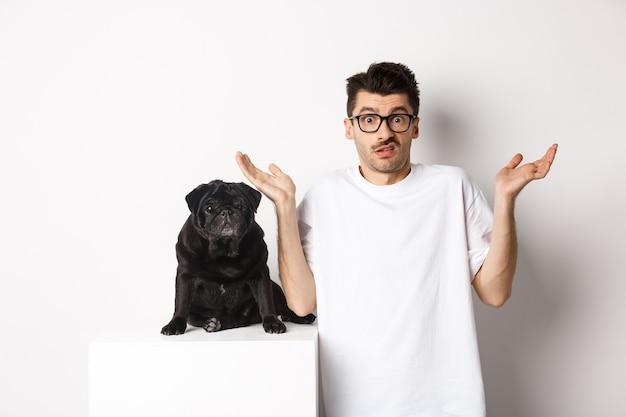 白い背景の上に黒いパグ犬の近くに立って、手を上げて複雑に肩をすくめる眼鏡をかけた混乱した男の画像。