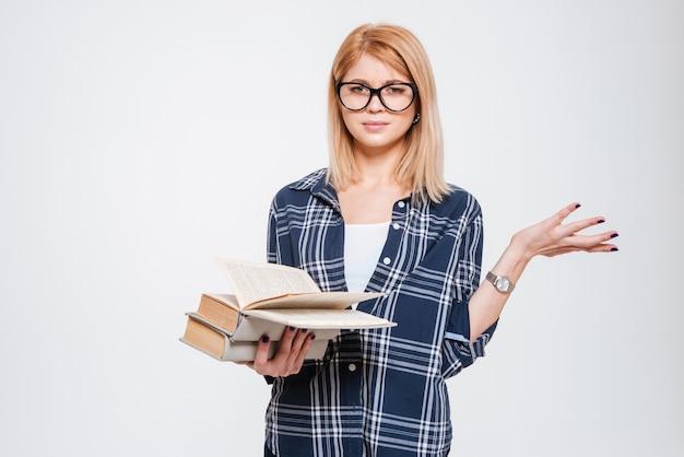흰색 배경에 고립 된 책을 읽고 혼란된 젊은 여자의 이미지.