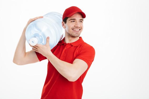 Изображение содержимого доставки курьером в красной футболке и кепке, перевозящих бутылку пресной воды в офис кулер, изолированных на пустое пространство