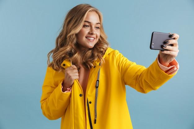 携帯電話を持って自分撮り写真を撮る黄色いレインコートを着た20代の女性のコンテンツの画像