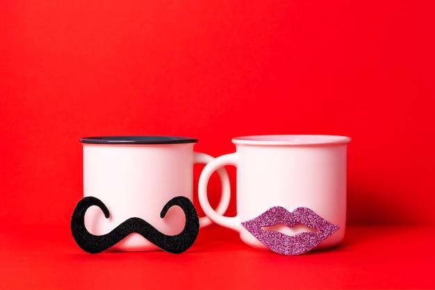 女性の唇と男性の口ひげを持つカップルの白いコーヒーカップの画像、バレンタインデーのお祝いのコンセプトでデート。