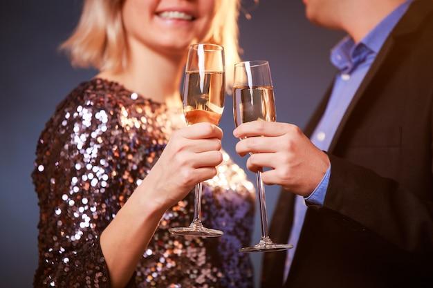 黒の背景にシャンパンとシャンパングラスとカップルの画像