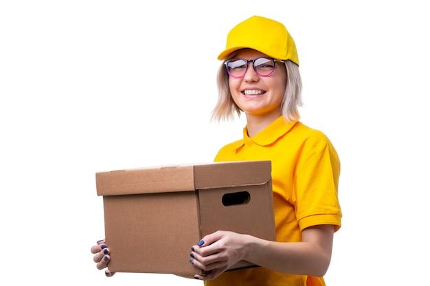 彼女の手に段ボール箱とメガネと黄色のtシャツを持つ宅配便の女性の画像