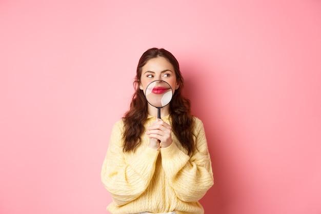 재미있는 것을 생각하는 수줍은 매력적인 소녀의 이미지, 입술 근처에 돋보기로 미소를 짓고, 분홍색 배경에 서서 홍보 텍스트를 옆으로 바라보고 있습니다.