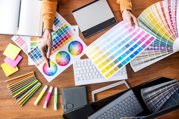 색상 선택 및 그래픽 태블릿에서 작업하는 창의적인 그래픽 디자이너 이미지