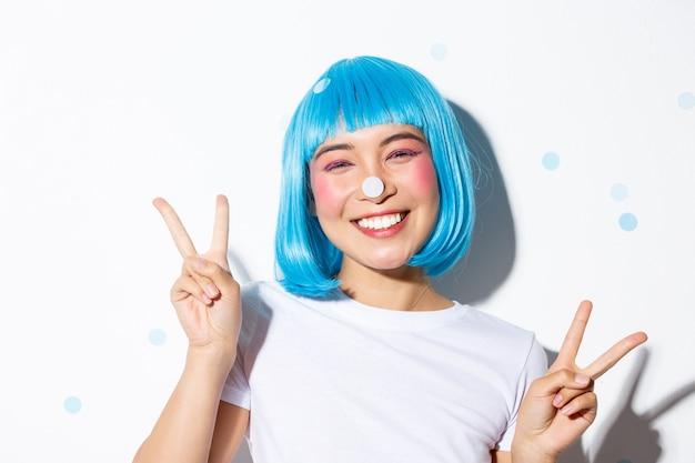 Изображение милой и глупой азиатской девушки с конфетти на носу, счастливой улыбающейся и показывающей жест мира