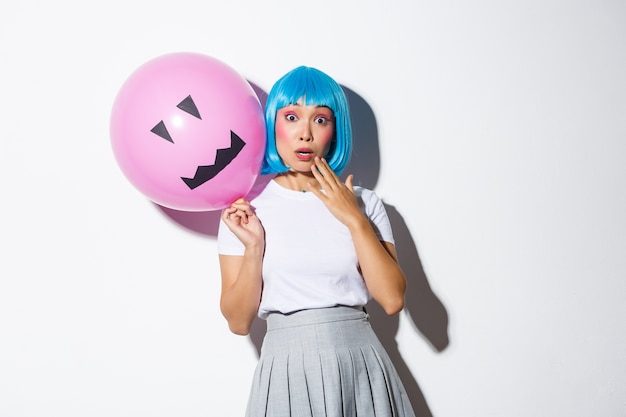 Изображение милой азиатской девушки в голубом парике, задыхаясь, удивлено, держа в руках розовый шар с страшным лицом, стоя.