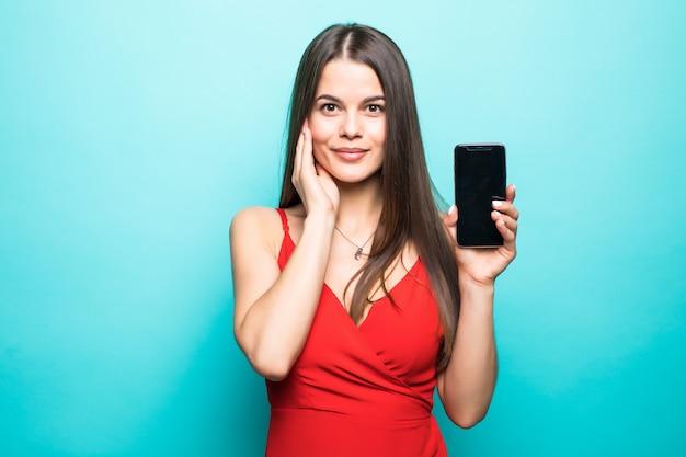青い壁に隔離されたかわいいかわいい若い女性の画像。携帯電話のディスプレイを表示しています。