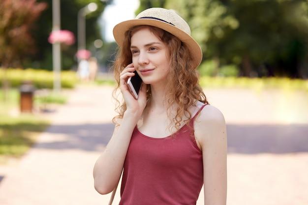 公園を散歩して、彼女の夏休みを楽しんで、耳の近くに携帯電話を持って、スピーカーを注意深く聞いて、カジュアルな服を着て、彼女の残りに満足しているかわいい優しい女の子の画像。