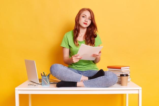 Изображение милой молодой женщины, сидящей возле ноутбука и книг во время работы или учебы