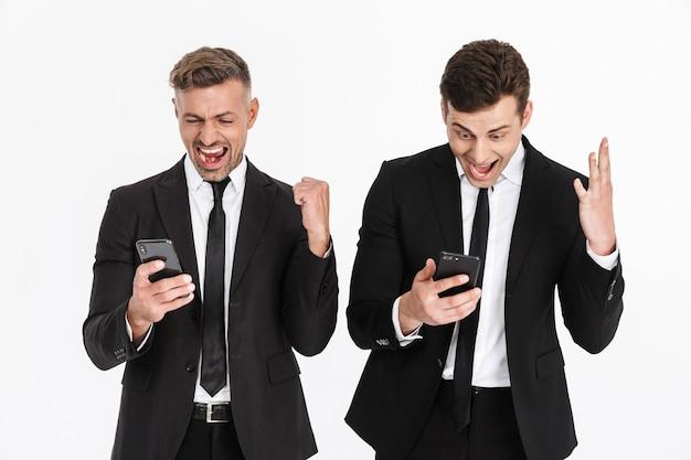 Изображение восхищенных кавказцев, двух бизнесменов в офисных костюмах, радующихся и кричащих, держа в руках изолированные мобильные телефоны