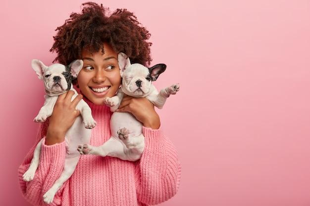 기뻐하는 여성 안주인의 이미지가 두 마리의 귀여운 강아지와 함께 포즈를 취하고, 행복하게 멀리 보이고, 애완 동물과 함께 사진을 찍습니다.