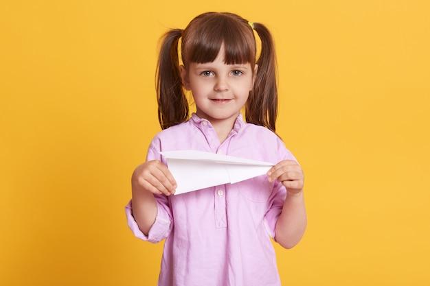 黄色の壁の上に孤立して立っている、両手で紙飛行機を持っている、楽しんで、ゲームをして、穏やかな表情をして喜んでいる肯定的な女の子の画像。
