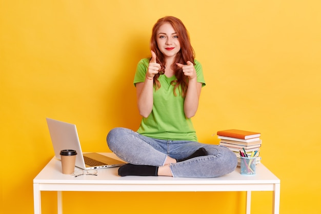 Изображение счастливой молодой женщины, указывая пальцем на камеру и улыбаясь