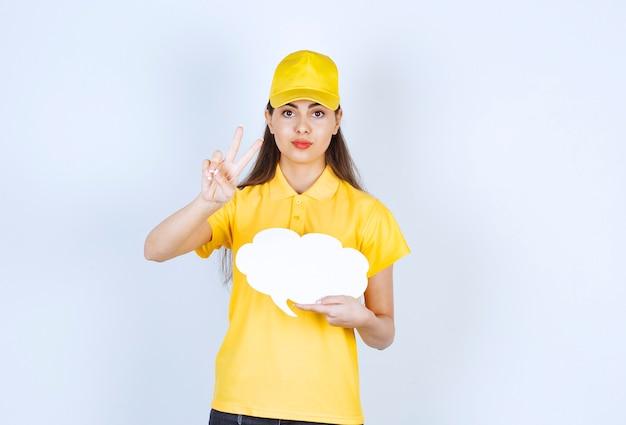 흰 벽 위에 말풍선을 들고 포즈를 취한 노란색 모자를 쓴 배달부의 이미지.