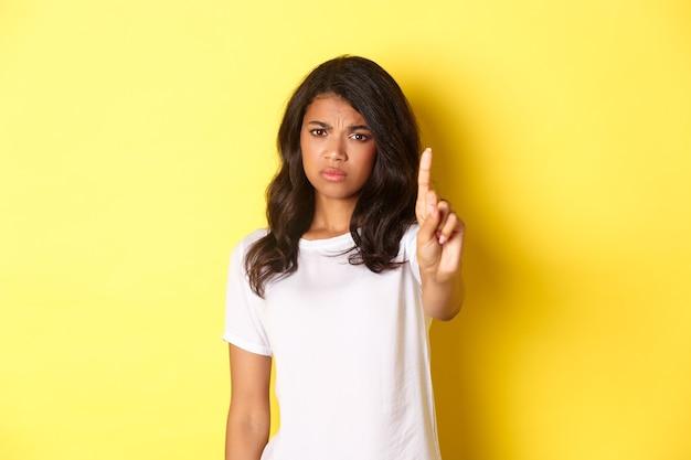 失望したアフリカ系アメリカ人の女の子がノーと言って、誰かを禁止または停止するために指を振って、人に反対し、黄色の背景の上に立っている画像。