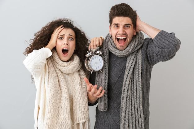 灰色の壁に隔離された、目覚まし時計を保持しながら叫んで不機嫌なカップルの男性と女性の画像