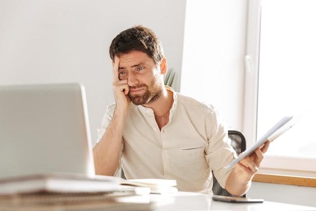 Изображение недовольного офисного работника 30-х годов в белой рубашке с ноутбуком и бумажными документами, сидящего за столом на современном рабочем месте