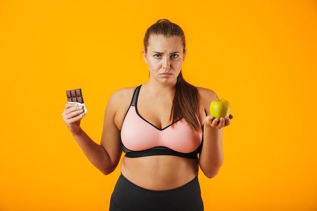 黄色の背景で隔離のチョコレートバーとリンゴを両手に持っているトラックスーツの不機嫌な太りすぎの女性の画像