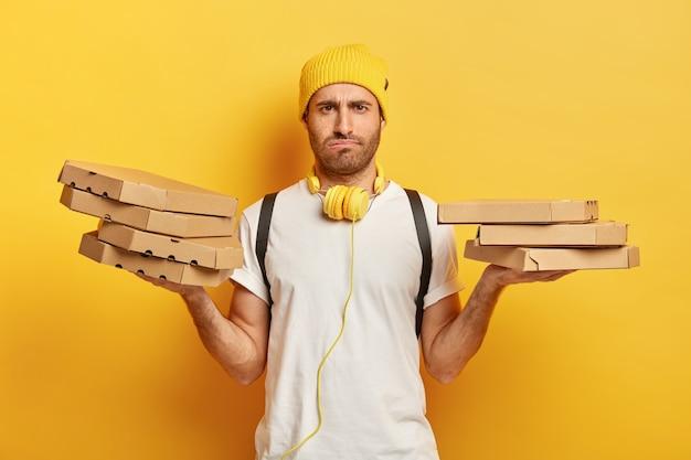Изображение недовольного белого мужчины с угрюмым выражением лица, держит картонные коробки из-под пиццы, чувствует усталость после доставки еды в течение всего дня, носит повседневную одежду, изолирован на желтой стене