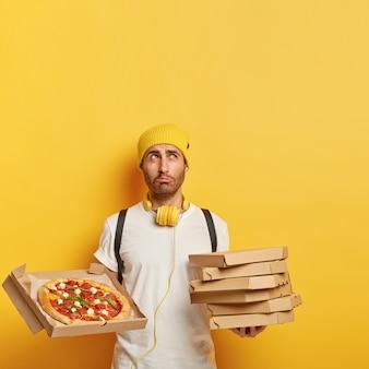 不満の配達人の画像は、段ボール箱の山を保持し、おいしいチーズピザを示し、悲しい表情をして、黄色い帽子と白いtシャツを着ています