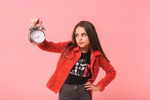 赤い壁の上に隔離され、立っている間、カジュアルな目覚まし時計を保持している不満の女の子8-9yの画像