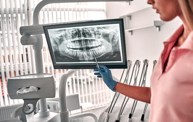 치아 엑스레이 필름으로 제시하는 의사 또는 치과 의사의 이미지는 직장에서 일하는 치과 및 치과 치료에 환자를 추천합니다.