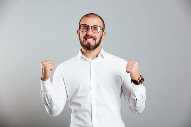 白いシャツと眼鏡の灰色の壁に分離された勝利で拳を握りしめている有頂天の白人男性のイメージ