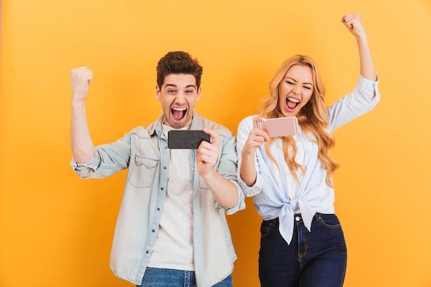 휴대 전화에서 비디오 게임을 함께하면서 기뻐하는 황홀한 남녀의 이미지