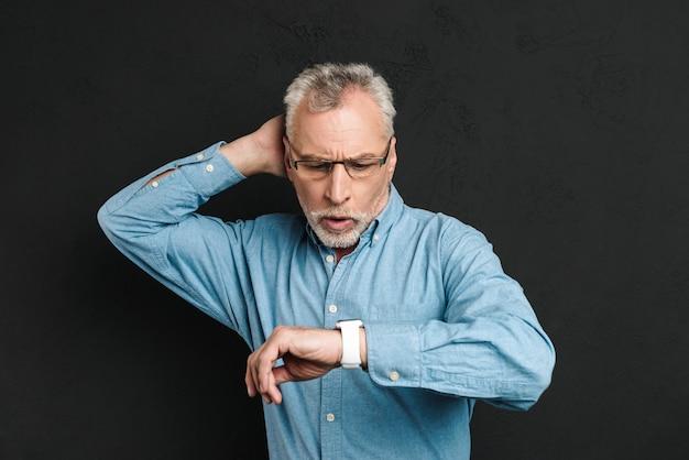 Изображение пожилого небритого мужчины 60-х с седыми волосами в очках смотрит на свои наручные часы с растерянностью, изолированных на черной стене