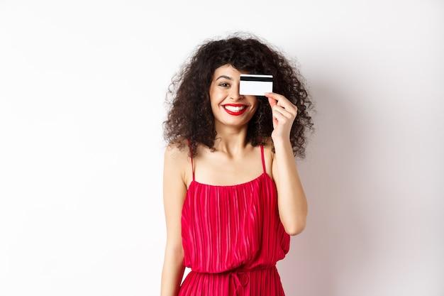 赤いドレスを着たエレガントな女性の画像。プラスチックのクレジットカードを表示し、カメラに向かって微笑んで、白い背景の上に立っています。コピースペース