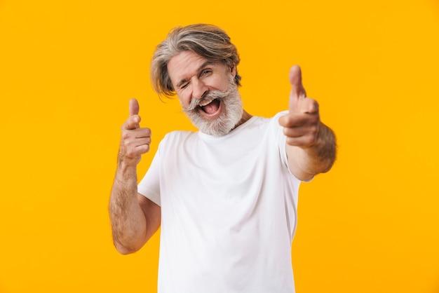 Изображение эмоционального жизнерадостного старшего седого бородатого мужчины позирует изолированным на желтой стене, указывая на вас.