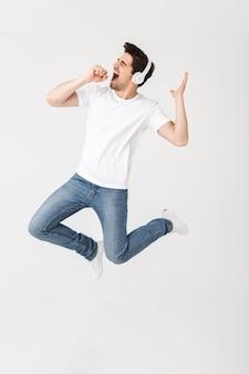 Изображение эмоционального возбужденного молодого человека, позирующего изолированным над белой стеной, слушая музыку с наушниками, поющими прыжками.