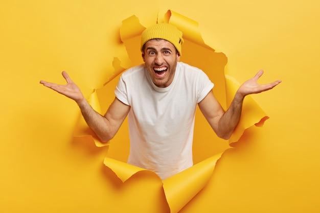 感情的な男のイメージは帽子と白いカジュアルなtシャツを着て、手を横に広げ、陽気な無知な表情をしています
