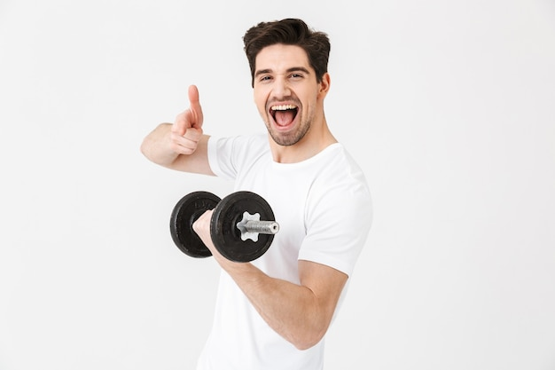 Изображение эмоционального счастливого возбужденного молодого человека представляя изолированного над белой стеной, держащей гантель, делает упражнение указывая.